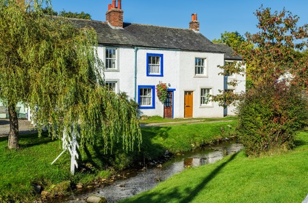 home exterior: Exterior of white home with stream  in Caldbeck village of Cumbria, England on sunny day.