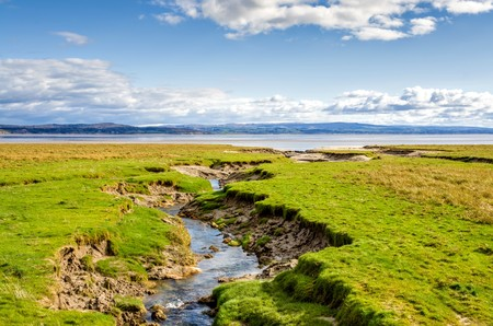 cumbria: Coastline by green fields at Grange-over-sands in Cumbria, England with blue skies and sunshine. Stock Photo
