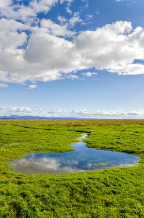 cumbria: Clouds in blue skies over green fields in English countryside along coastline at Grange-over-sands in Cumbria, England. Stock Photo