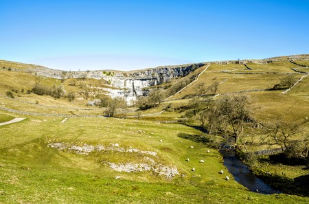 beck: Malham Beck and Cove, North Yorkshire England, with a patchwork of dry stone walls. Stock Photo