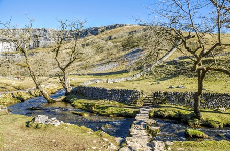 beck: Low bridge over Malham Beck near Malham Cove in attractive landscape with footpath and gate in the stone wall. Stock Photo