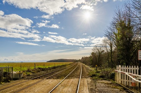 recedes: Pedestrian railway crossing over a track in the countryside. Stock Photo
