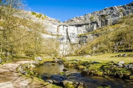 cove: Limestone cliffs of Malham Cove in North Yorkshire, England on sunny day.