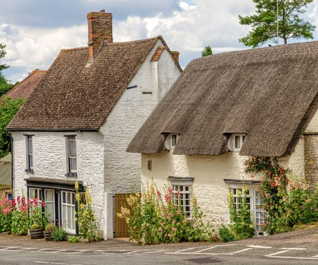 Stone cottages along roadside in the village of Great Milton in Oxfordshire, England with summer flowers on sunny day.