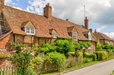 Gardens in front of row of cottages in the village of Turville, Buckinghamshire, England with blue skies.