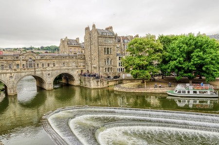 Aerial view of Pultney Bridge and Weir on River Avon with boat in Bath, England in daylight with overcast skies. United Kingdom. Фото со стока - 61559933