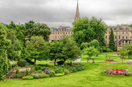 Flower beds, grass and trees in public park of Bath, England on grey overcast day. Stock Photo