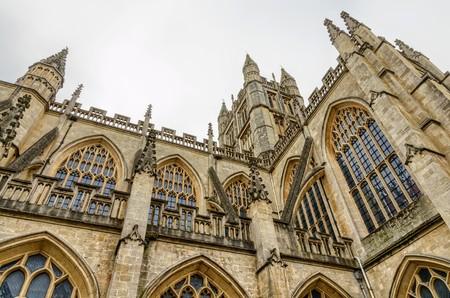 Facade of tower in Bath Abbey in Bath, England in daylight.