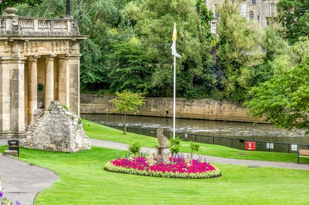 Flower beds in green lawn outside historic stone buildings of Bath, England along River Avon.