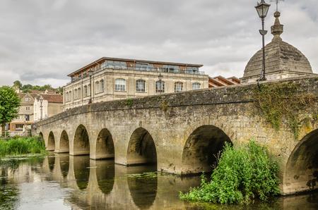 Old stone bridge over River Avon in Bradford on Avon, Wiltshire, England on overcast day.