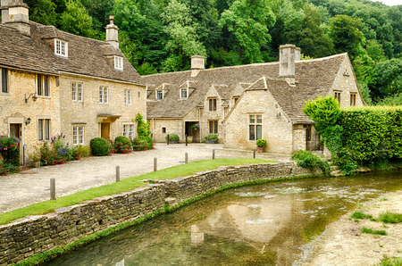 old english: A large villa in Castle Combe village with a spacious yard and a creek next to it.