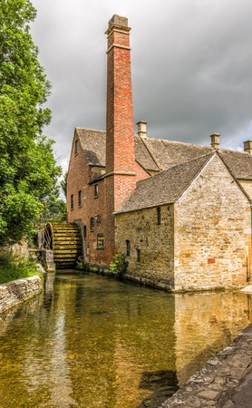 intact: 19th century watermill in the English Cotswold village of Lower Slaughter showing the intact waterwheel, chimney and river which powers the mill.