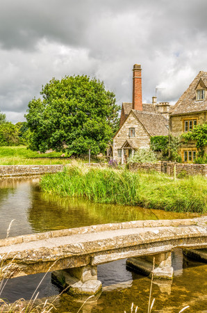 Footbridge over River Eye at Lower Slaughter in the English Cotswolds, with historic houses and watermill in the background. Stock Photo