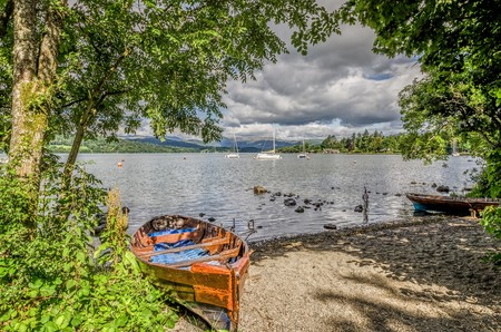 Dilapidated rowing boat pulled up onto sandy shore of Lake Windermere in the English Lake District, Cumbria. Stock Photo