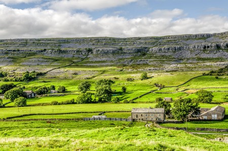 Farm house in green fields of the Yorkshire Dales near Ingleton, England on sunny day. Stock Photo