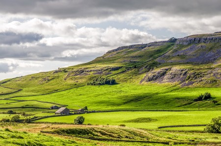 Green hillside of the Yorkshire Dales near Ingleton, England with cloudy skies.