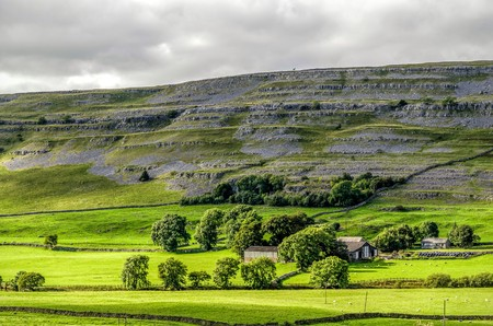 Farm house in green valley of Yorkshire Dales near Ingleton, England.