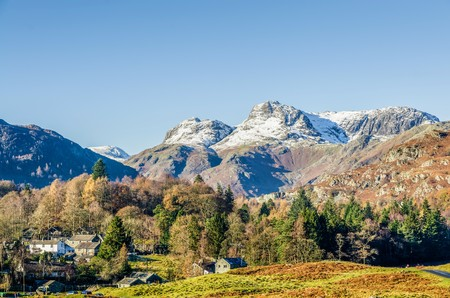 langdale pikes: The Langdale Pikes over the village of Elterwater, Langdale, English Lake District, UK on sunny day with blue skies. Stock Photo