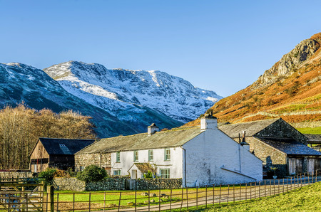 Whitewashed farmhouse and barn at Langdale in the English Lake District with snow covered fell behind and blue sky background.