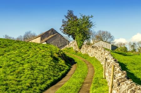Winding lane leading uphill to a barn Stock Photo