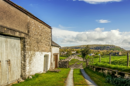 An old barn in Cumbria on a sunny day with a wooden gate and distant hills.