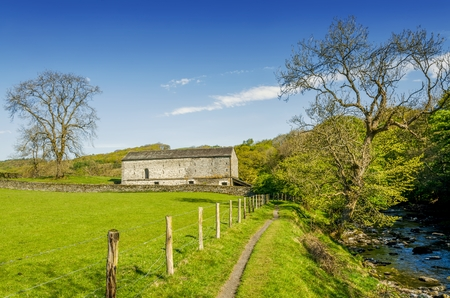 An isolated barn set in green English countyside by a path running alongside a river. Stock Photo