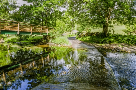 Footbridge and ford on a stream in a wooded area. Stock Photo