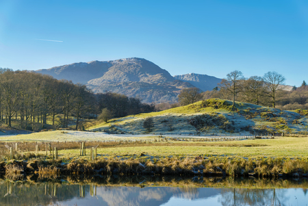 The English Lake District mountain known as Wetherlam, seen from the calm waters of Elterwater