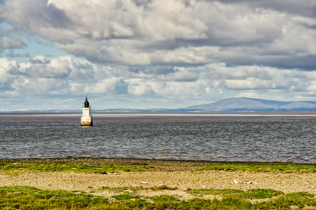 Plover Scar lighthouse at the entrance to the Lune estuary. 免版税图像