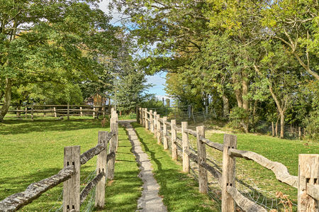 A rural footpath passing between two wooden fences.