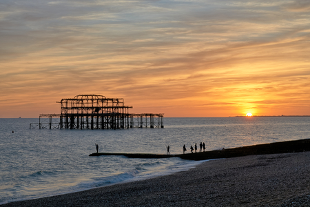 The ruins of Brightons West pier silhouetted against a setting sun.