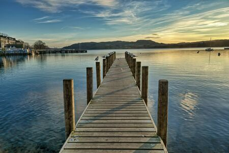A view of a jetty on Windermere at sunset.