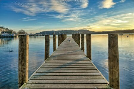 A jetty on a calm Windermere at sunset.