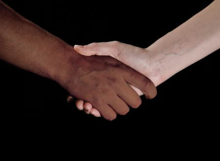 racism: Black and white hand shaking together in friendship or partnership