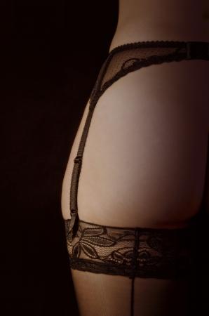 garter belt: detail of a black garter belt with stockings on his left leg