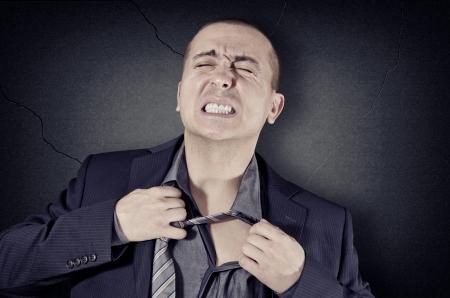 worried man: A man pulls a tight tie