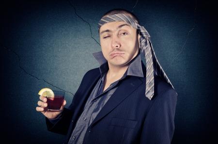 ubriaco: Uomo d'affari ubriaco con cravatta in testa e un bicchiere in mano