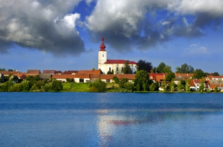 reflection of the church and village in the lake photo