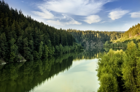 water reservoir between forests under clouds photo