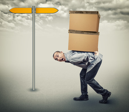 heavy lifting: A man carries two heavy boxes Stock Photo