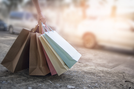 Women carry shopping bags of many colors in hand, discount shopping concept. Stockfoto