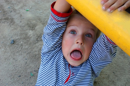 The little boy on a childrens playground. The surprised look. The scared look. Soft focus. photo