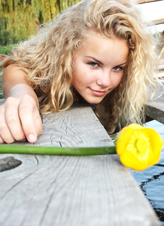 Portrait of the beautiful young girl of the blonde and curly hair against trees and river with a yellow lily.