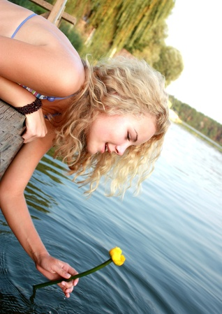 blonde curly hair: Portrait of the beautiful young girl of the blonde and curly hair against trees and river with a yellow lily.