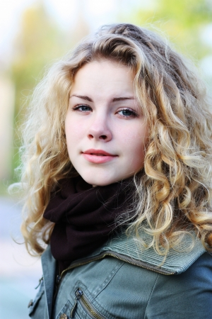 Blonde girl with curly hair on natural background