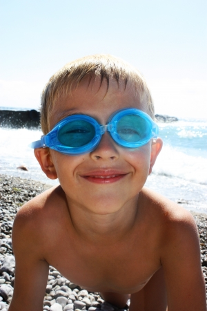 Funny boy in sunglasses on the beach  photo