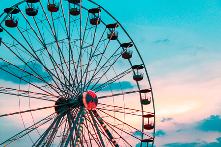 Ferris wheel without people moving slowly in the blue sky