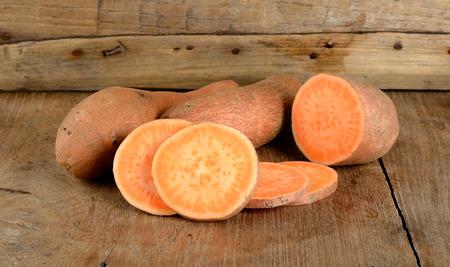 batata: Sweet potato on the wooden background .