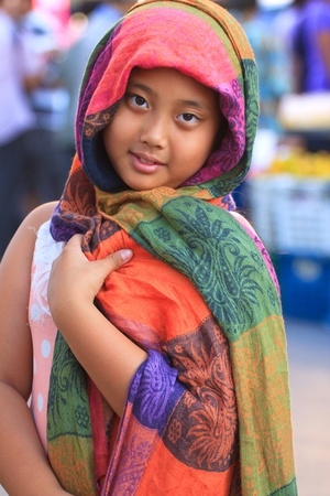 girl and colorful silk clothes cover her head photo