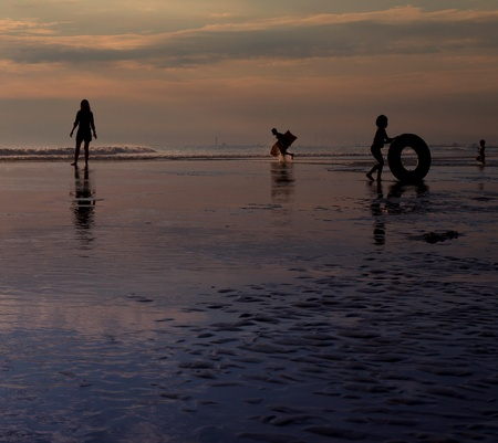 silhouette of people in activities on the sea beach photo